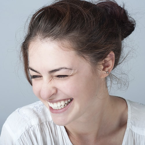A young woman laughing with a bright smile to illustrate cosmetic dentistry services at this dentist in Marysville, OH