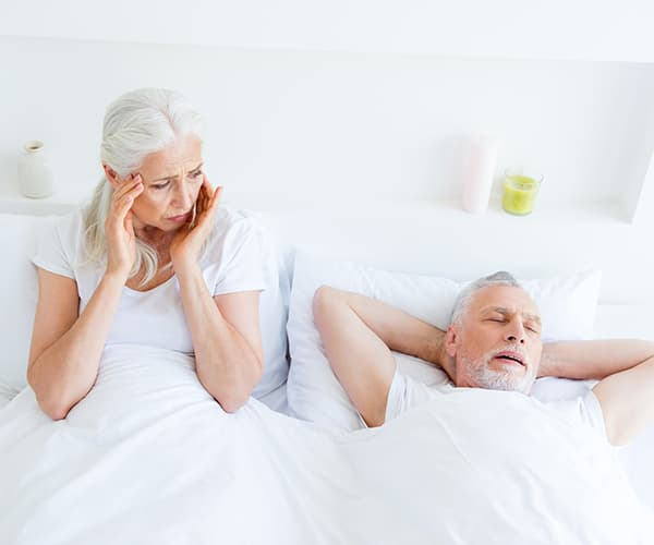 A older woman who cannot sleep because of her snoring husband who has sleep apnea